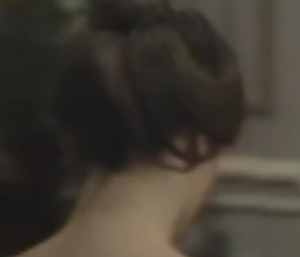 a white woman's head from behind. She has brown hair that is pinned up