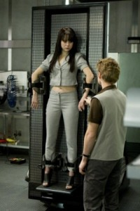 Image of a dark haired white teen girl (Zoe Graystone from Caprica) in a case where a robot should be. She is attended to by a technician, seen from the back, who appears to be a young white male.
